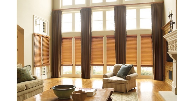 Charlotte great room with natural wood blinds and full-length drapes.