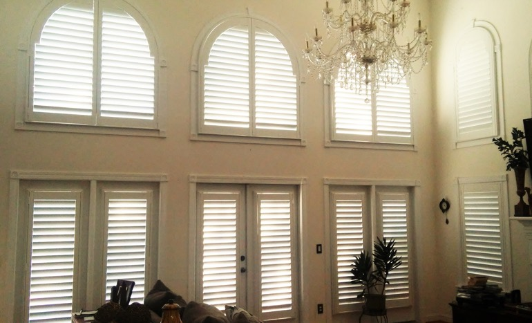 Television room in two-story Charlotte house with plantation shutters on high windows.