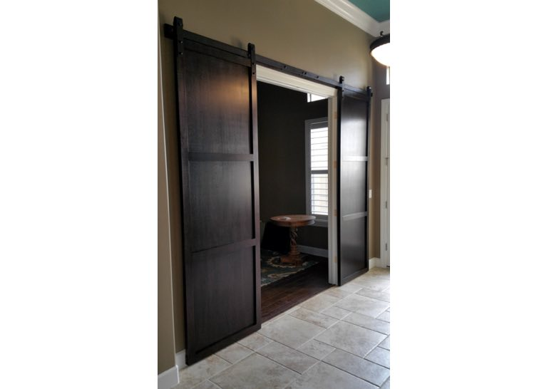 Dark brown sliding barn door covering home office entry