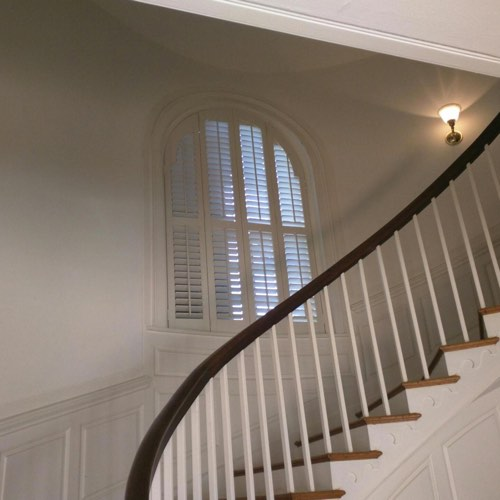 White plantation shutters covering rounded window located in spiral stairwell.