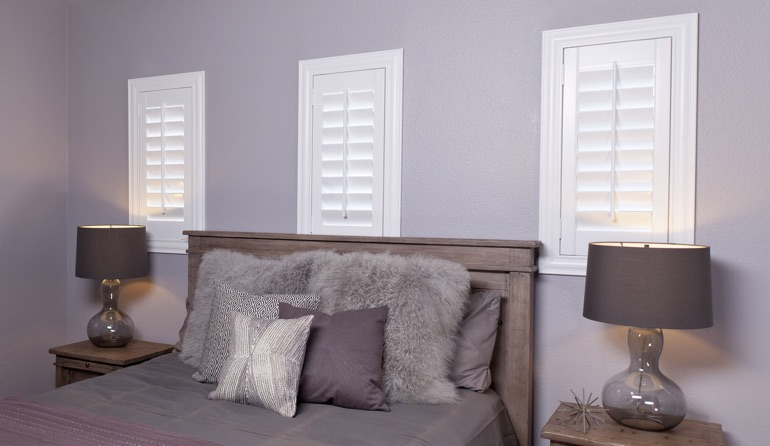 White plantation shutters in Charlotte bedroom windows.