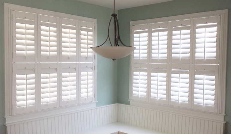 Pastel green wall in Charlotte kitchen with shutters.