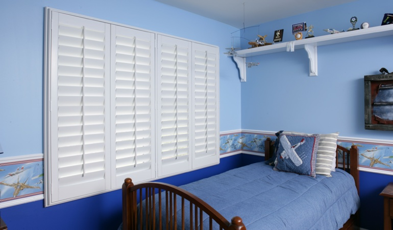 Large plantation shutters covering window in blue kids bedroom in Charlotte